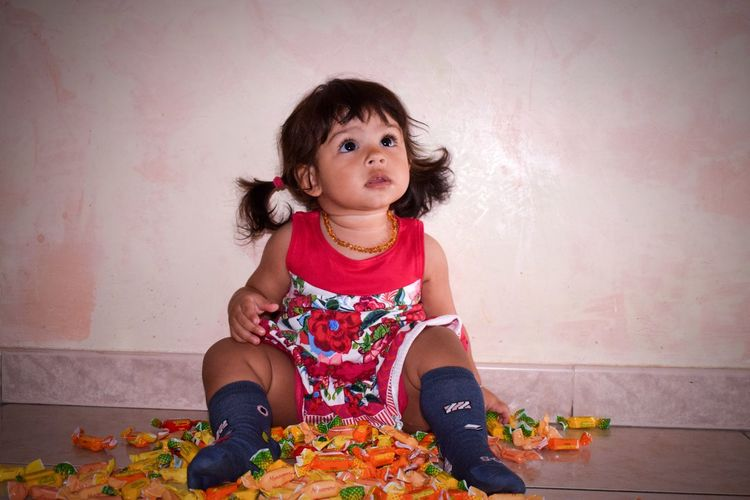 Cute girl with candies sitting on floor against wall