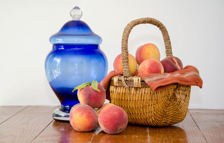 ripe sweet peaches with a blue glass jar Agriculture Basketball Fall Colors Freshness Nature Still Life Photography USA Basket Container Food Food And Drink Freshness Fruit Healthy Eating Indoors  Juicy Fruit Michigan Peaches Orange Color Organic Peanuts Peach Still Life Table Wellbeing Wood - Material Yellow