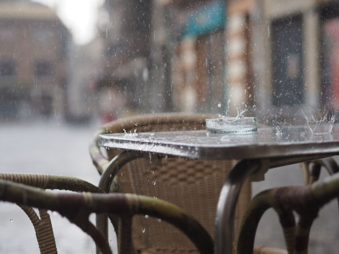 Raindrops Making Water Crown On Table By Chairs At Sidewalk Cafe In City