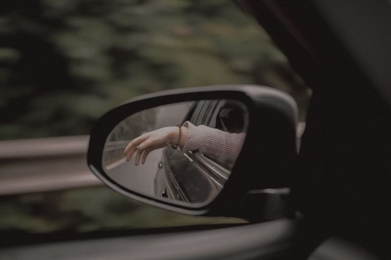 Reflection of hand on side-view mirror of car