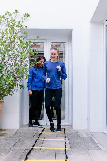 Women exercising against house