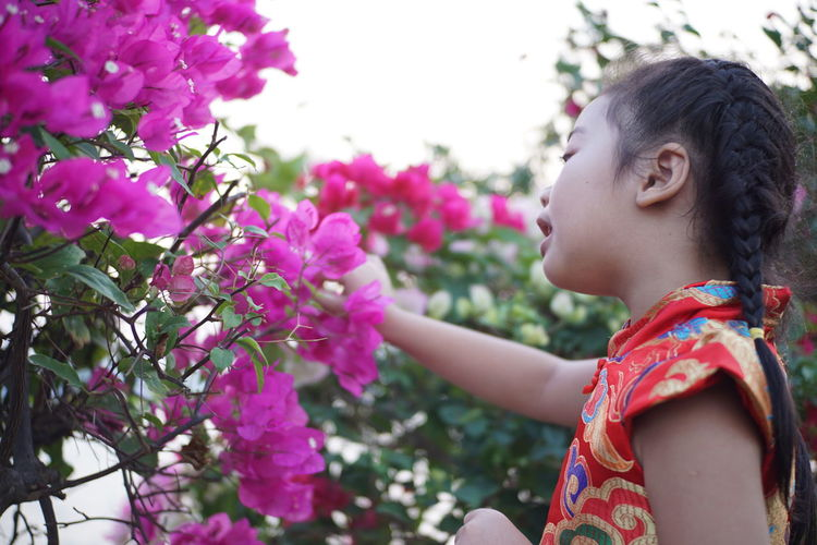 Low angle view of girl by pink flowering plants against sky