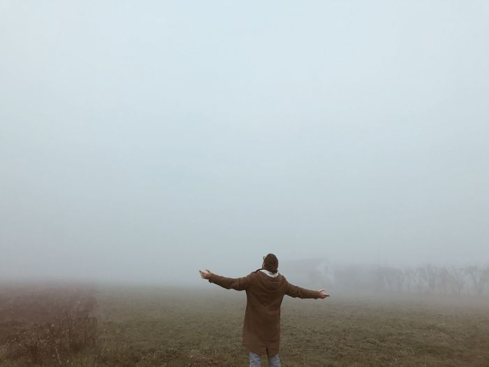 Rear view of man with arms outstretched on field against sky