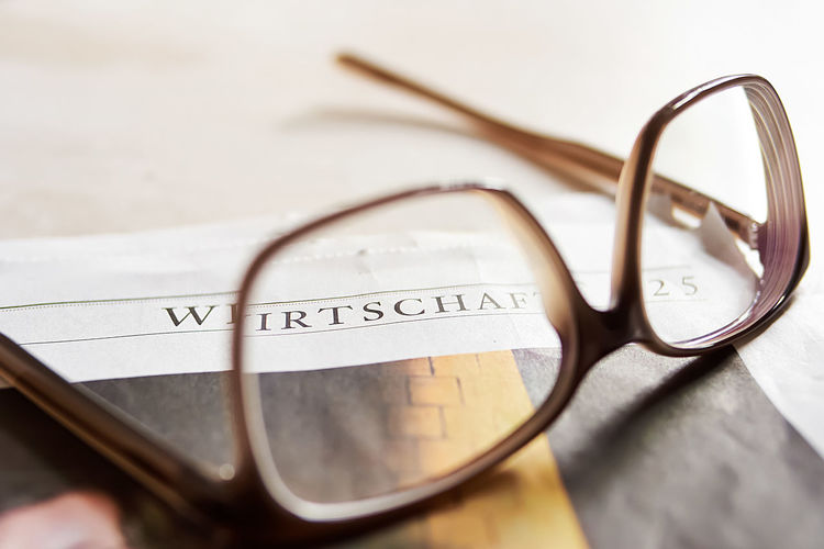 Close-up of eyeglasses on newspaper at home