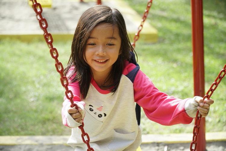 Smiling girl swinging in playground