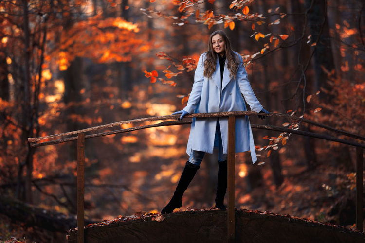 Full length of woman standing by trees in forest during autumn