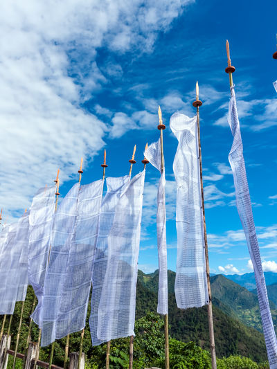 Low angle view of white flags hanging against sky