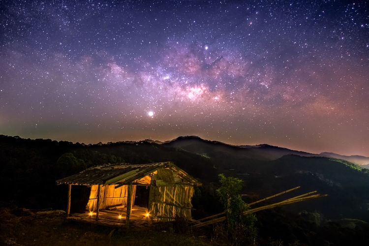 Illuminated broken house on mountain against star field sky