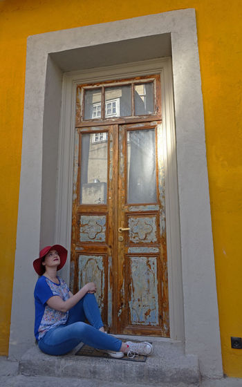 Woman sitting on closed door of building