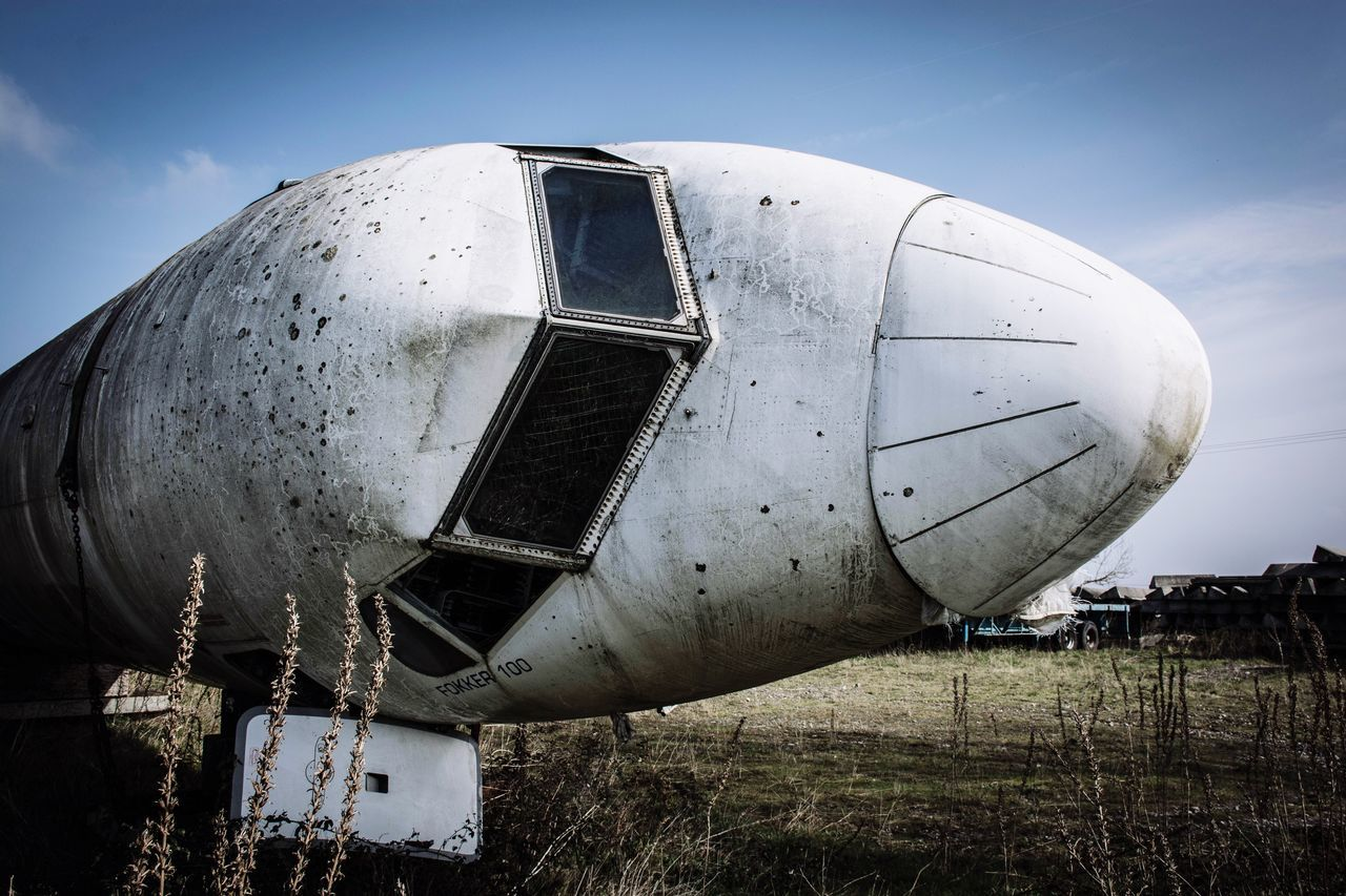 Close-Up Of Abandoned Airplane On Field Against Sky