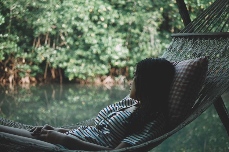 Thoughtful woman relaxing in hammock against lake