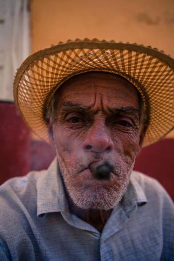 A cuban man poses for tourist' pictures. Cuba Cuban Leisure Activity Lifestyles Man Mid Adult Men Old Man People Portrait Portrait Photography Sigar Smoke Strawhat Strawhatportraits Trinidad Trinidad, Cuba