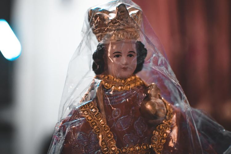 Close-up of woman figurine wrapped in plastic