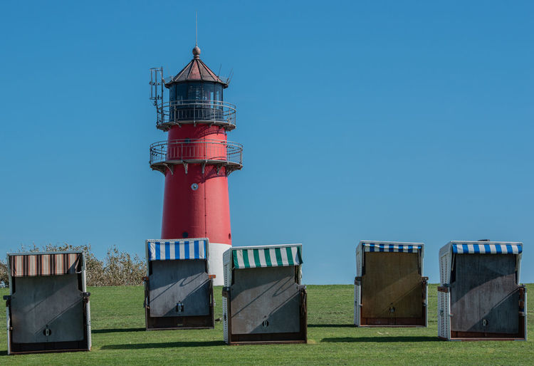 Lighthouse and hooded beach chairs against clear blue sky