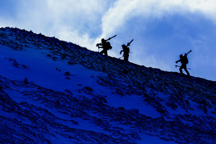 Low angle view of silhouette people on rock against sky