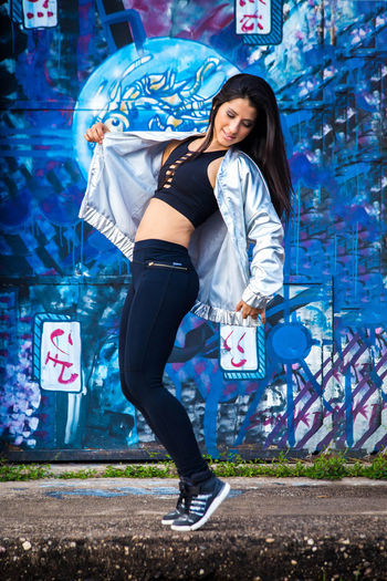 Full length of smiling young woman standing against graffiti wall