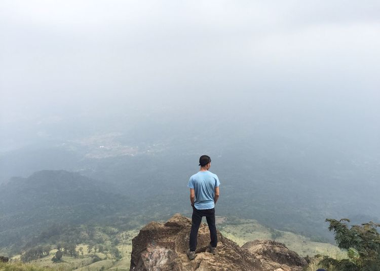 Rear View Of Young Man Standing On Mountain During Foggy Weather