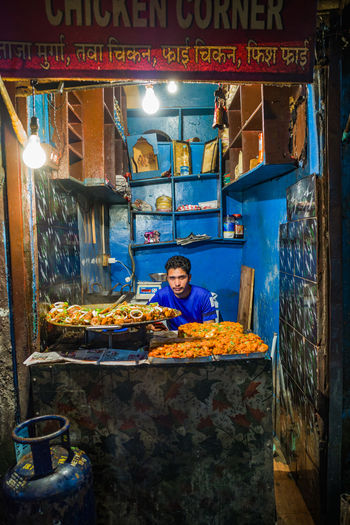 High angle view of man working at illuminated store