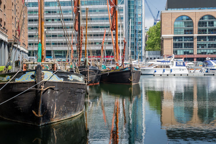 Sailboats moored in canal by buildings in city
