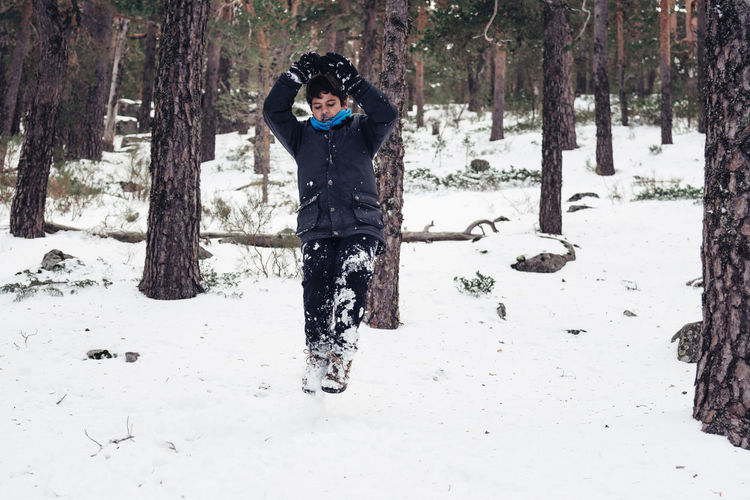 Full Length Of Boy Playing With Snow In Forest