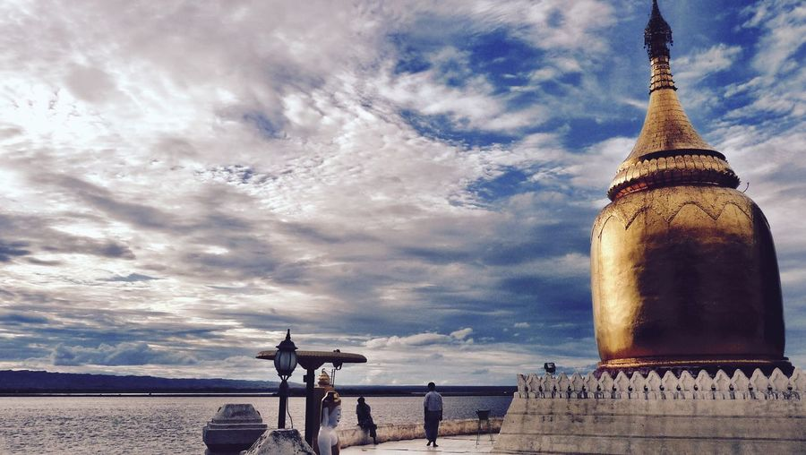 Golden stupa by river against cloudy sky