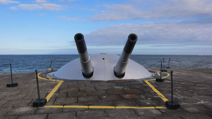 Canons on pier against sky