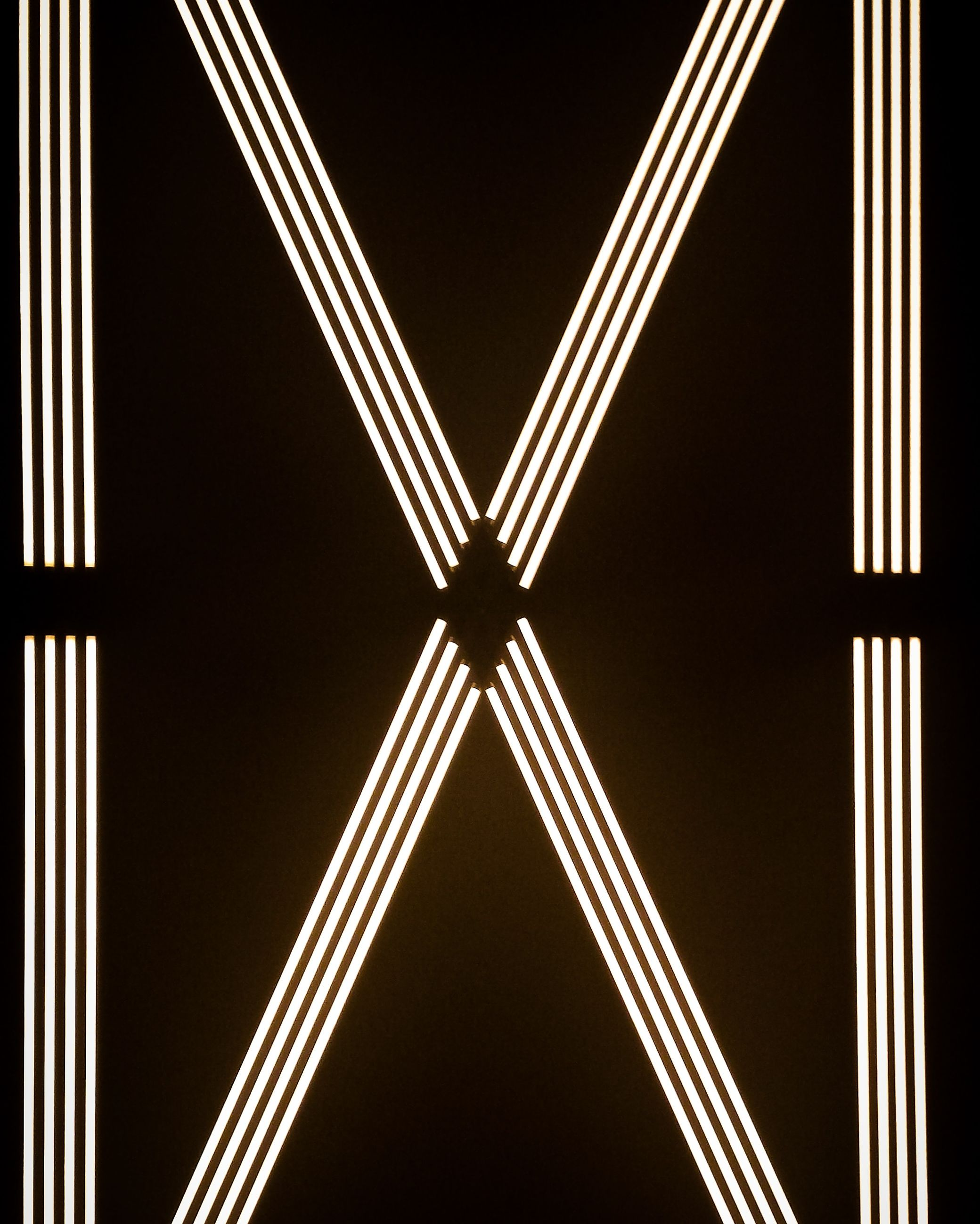 pattern, indoors, metal, no people, full frame, close-up, backgrounds, illuminated, lighting equipment, design, black background, architecture, abstract, shape, glowing, built structure, symmetry, low angle view, striped, night, ceiling, directly below, steel