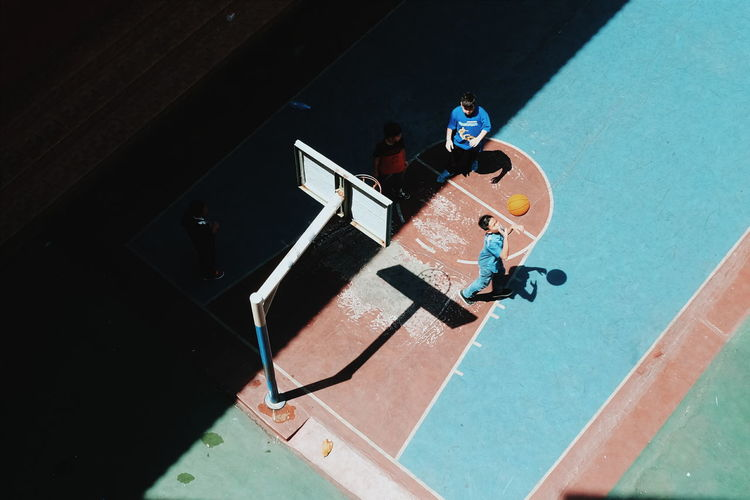 High Angle View Of Boys Playing Basketball At Court