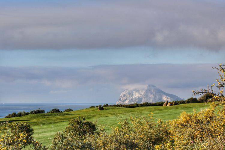 Rock of gibraltar by landscape against sky