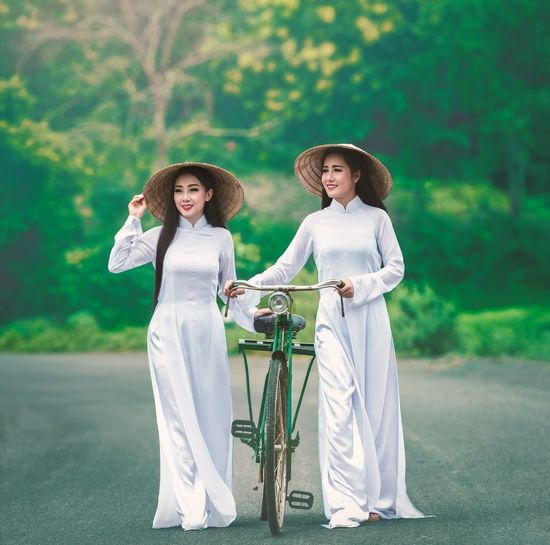 Women wearing white clothing and asian style conical hats while walking with bicycle on road