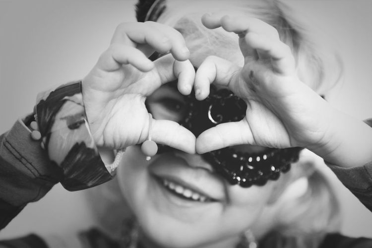 Portrait of happy girl making heart frame with fingers