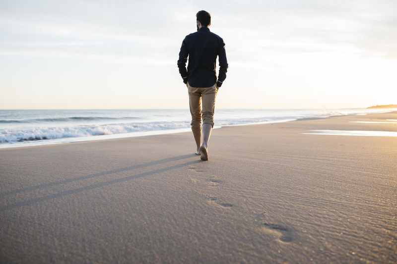 Adultman walking on a sand beach at sunset. Alone Freedom Freelance Life Man Sunlight Beach Bearded Businessman Casual Clothing Feet FreeTime Handsome Lifestyles Nature One Person Outdoors People Relaxation Sand Sea Sky Sunset Traveler Walking Water