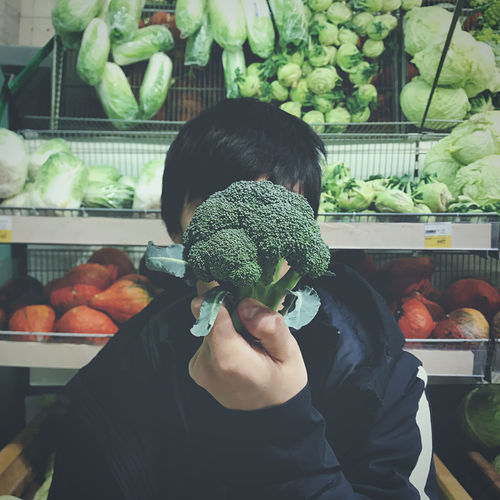 Man holding broccoli at market