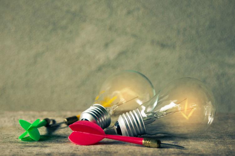Illuminated Light Bulbs And Darts Against Wall