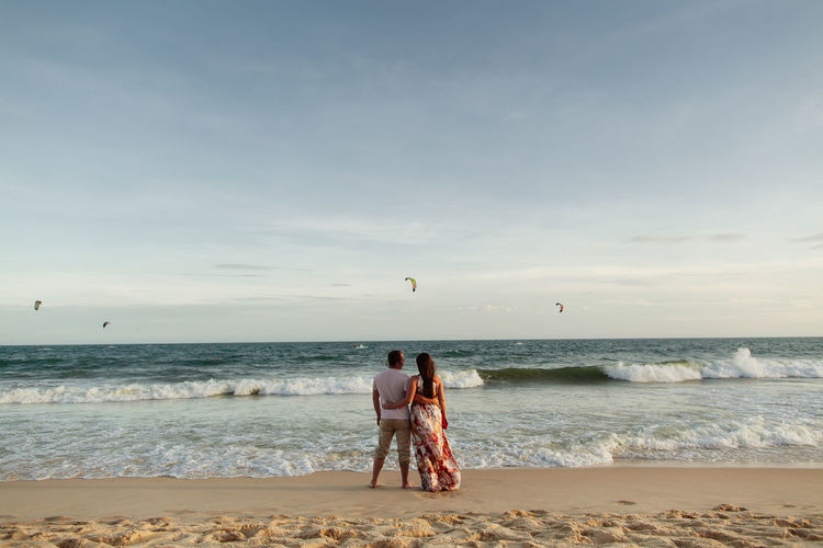 Rear view of couple standing on beach against sky