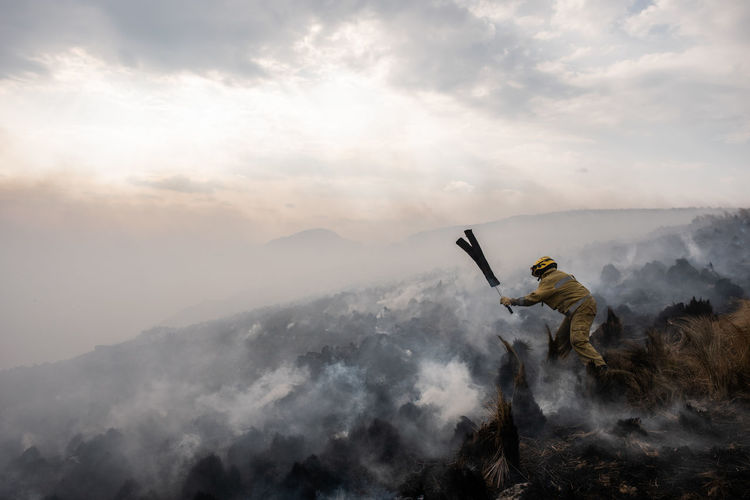 Full length of firefighter extinguishing fire on field