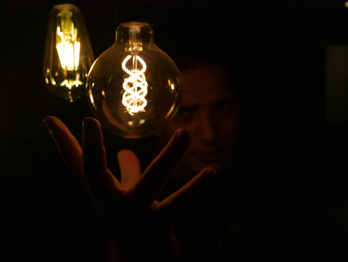 Close-up of man hand under illuminated light bulb