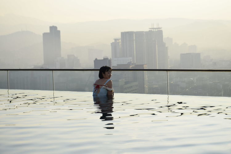 Rear view of woman in infinity pool against buildings during sunset