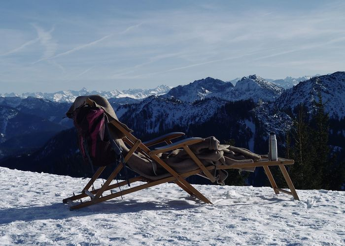 View of deck chair on snow covered land against sky
