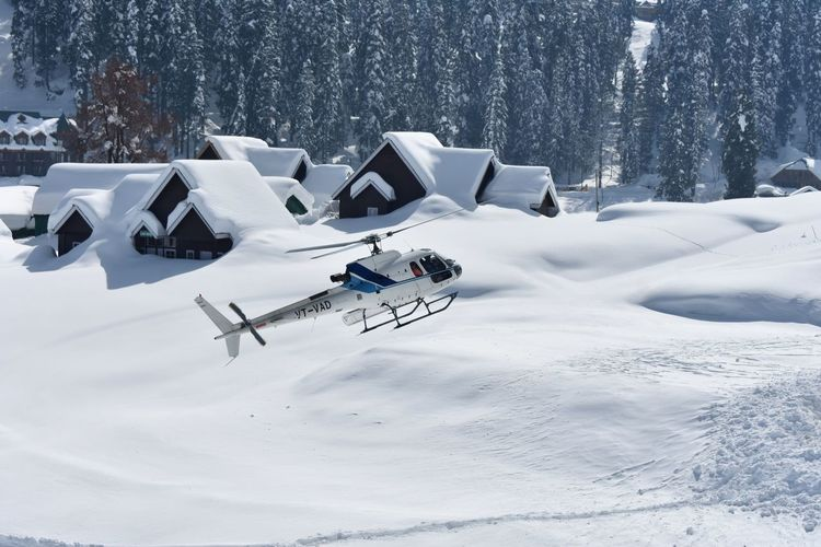 A chopper carrying tourists to the higher reaches at Gulmarg takes off during sunshine Snow Cold Temperature Winter Full Length High Angle View Business Finance And Industry White Color Sky