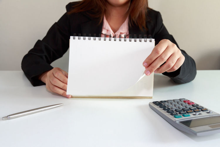 Midsection Of Businesswoman With Spiral Notebook On Table