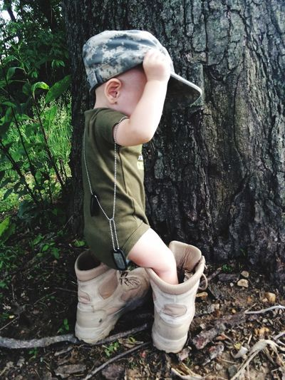 Cute Toddler Wearing Military Boots And Cap Against Tree