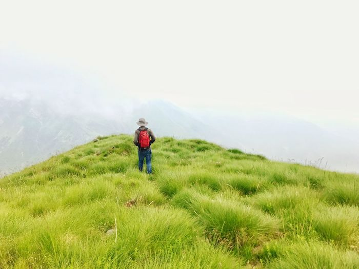 Rear View Of Man With Backpack And Hat Standing On Grassy Field During Foggy Weather