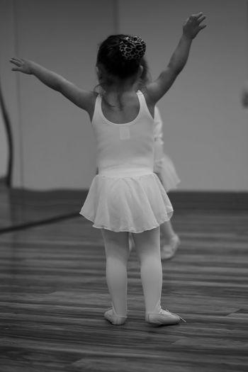 Ballerina girl dancing on floorboard at ballet studio
