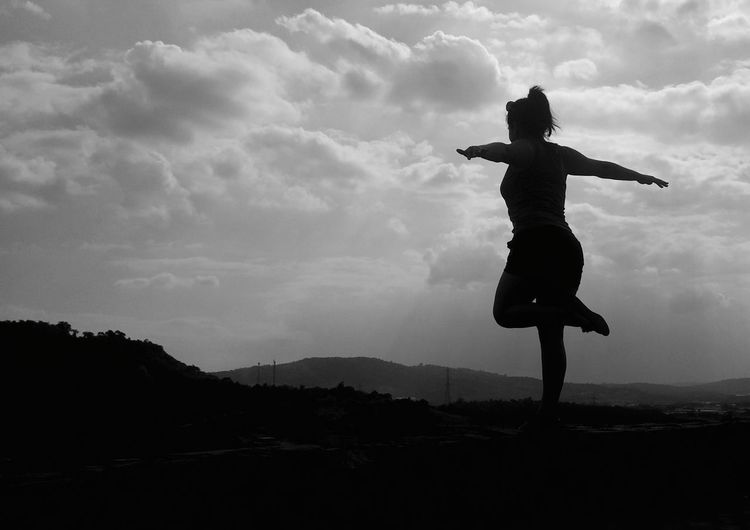 Woman doing yoga on landscape against sky