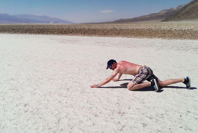 Full Length Of Shirtless Man Kneeling On Sand At Desert