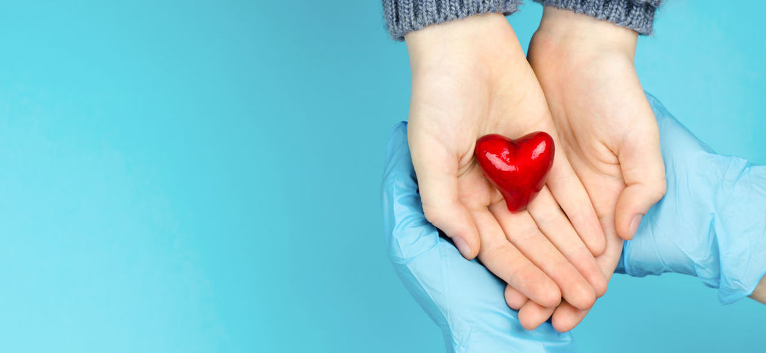 Midsection of woman holding heart shape against blue background