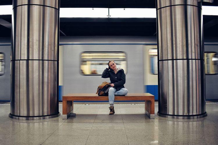 Full length of woman sitting on subway platform