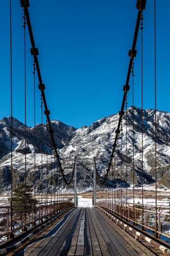Railroad tracks by snowcapped mountains against clear sky