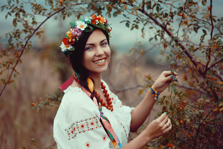 Portrait of smiling young woman standing by tree
